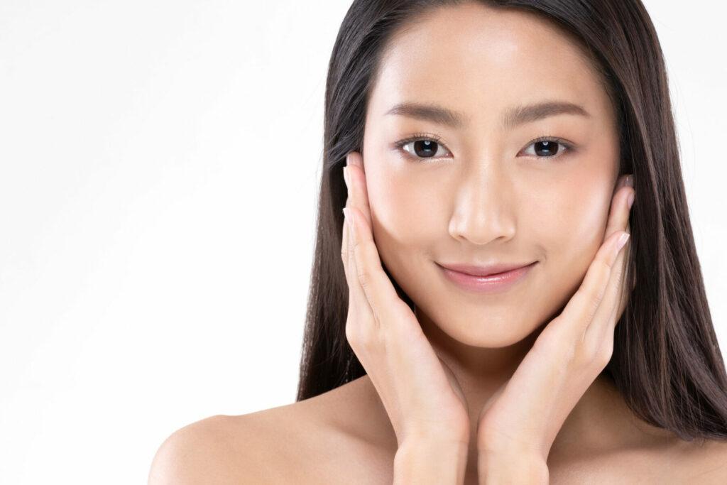 Asian woman touching soft cheek