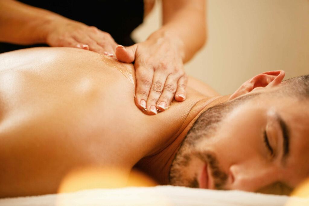 man having back massage with honey